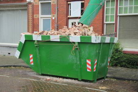 Loaded green trash bin rental with demolition debris for recycling