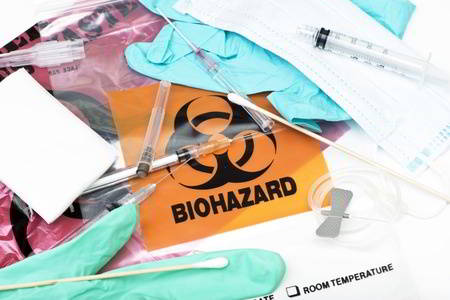 Biohazard medical waste bags with used syringes, needles, bandages, and other medical waste.