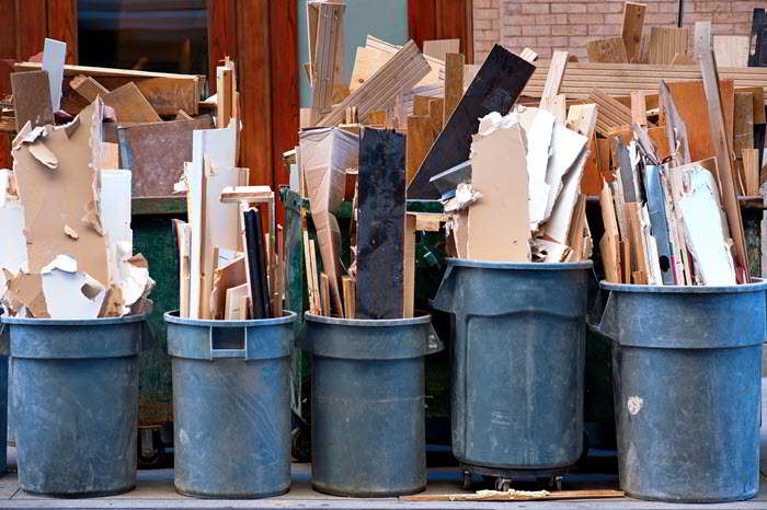 Row of garbage bins with construction debris on sidewalk